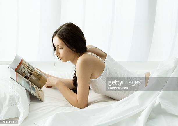 Young woman lying in bed looking at magazine