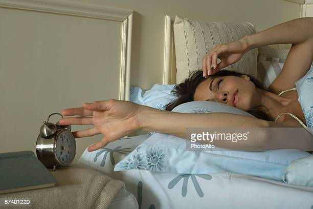 Young woman lying in bed, silencing alarm clock