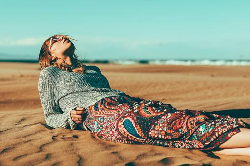 Young woman lying in desert landscape - gettyimageskorea