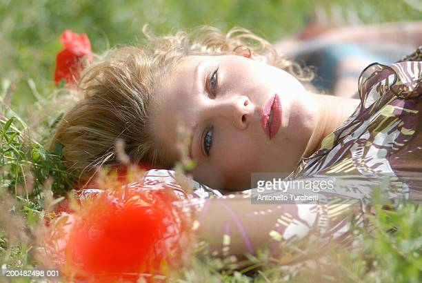 young woman lying in field, portrait - one young woman only stock pictures, royalty-free photos & images