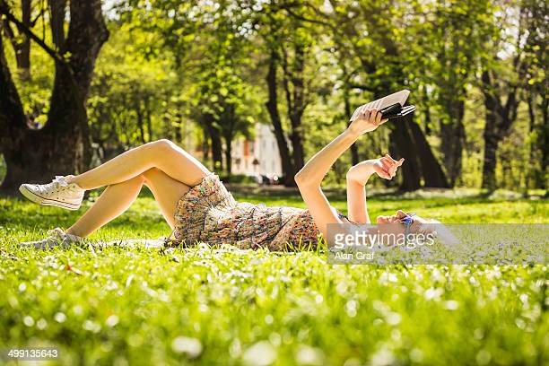young woman lying in forest taking selfie on digital tablet - grünes kleid stock-fotos und bilder