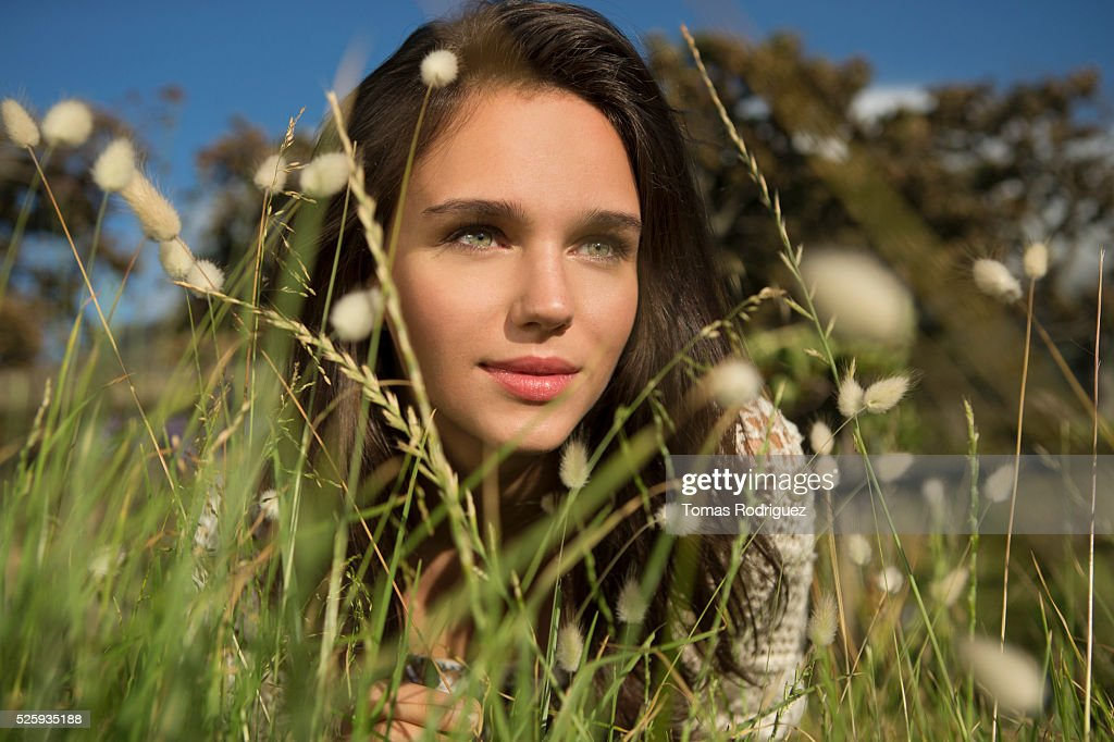 Young woman lying in grass : Stock Photo