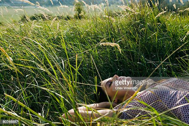 young woman lying in grass. - lying down foto e immagini stock