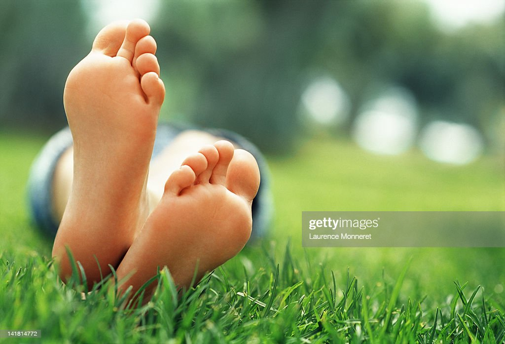 Young woman lying in grass with crossed feet : Stock Photo