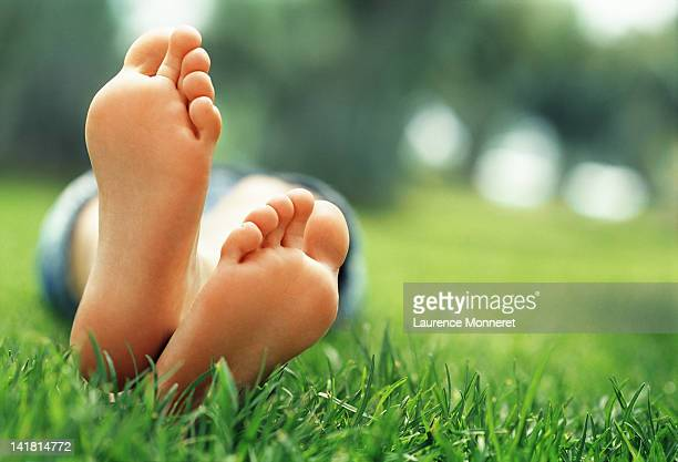 young woman lying in grass with crossed feet - female feet soles stock photos and pictures