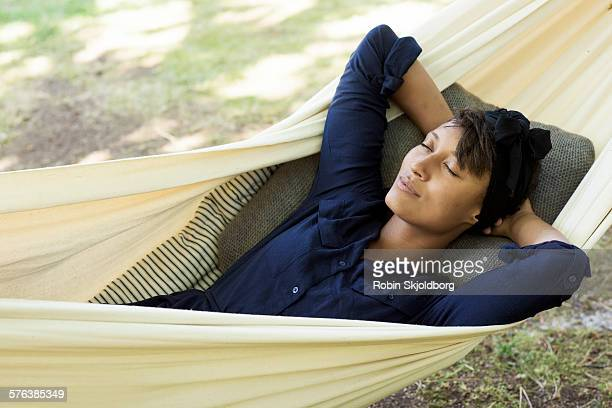 young woman lying in hammock with closed eyes - navy blue stock pictures, royalty-free photos & images