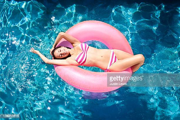 young woman lying in inner tube in luxury pool