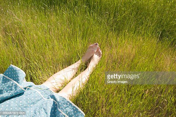 Young woman lying in long grass, low section