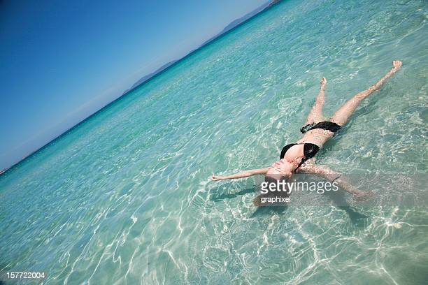 young woman lying in shallow tropical sea - whitehaven beach stock photos and pictures