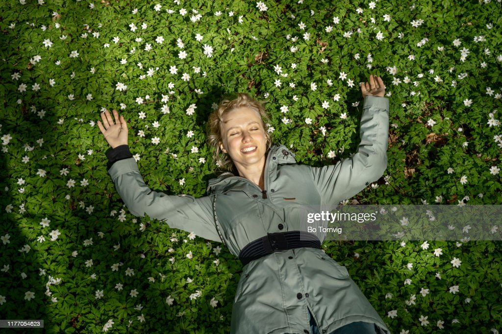 Young woman lying in the forest floor : Stock Photo