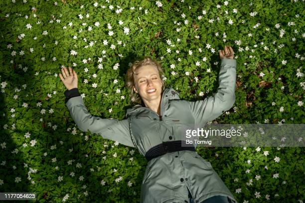 young woman lying in the forest floor - bo tornvig stock photos and pictures