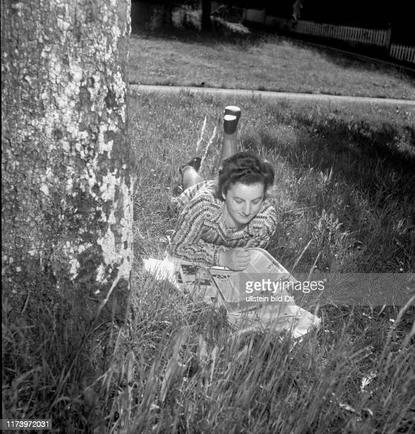 Young woman lying in the gras, reading a newspaper; Aesch 1948 Young woman lying in the gras, reading a newspaper; Aesch 1948