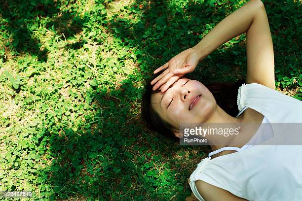 young woman lying in the grass,healthy lifestyle - lying down ストックフォトと画像