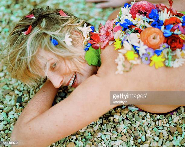young woman lying naked on pebbles with flower petals on back - maya desnuda fotografías e imágenes de stock