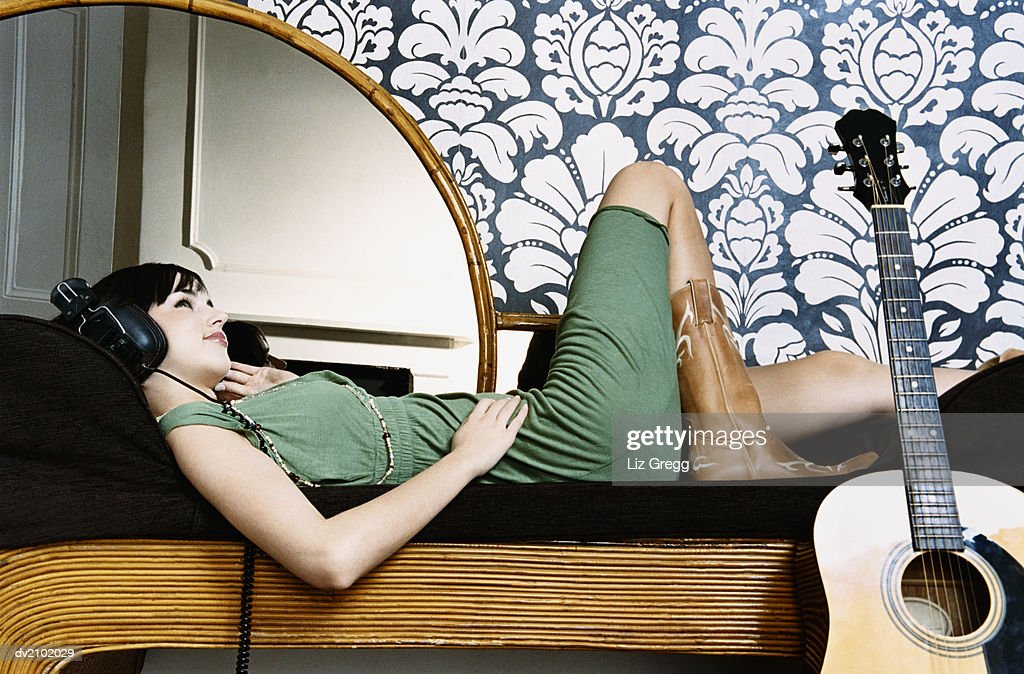 Young Woman Lying on a Chaise Lounge and Listening to Music on Headphones : Stock Photo