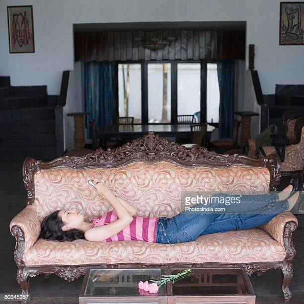 Young woman lying on a couch and operating a mobile phone