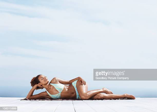 Young woman lying on a porch sunbathing