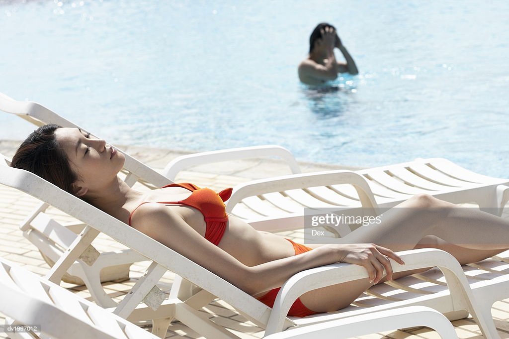 Young Woman Lying on a Sun Lounger Poolside Sunbathing : Stock Photo