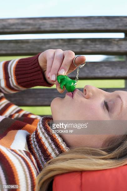 Young woman lying on a wooden bench with a key ring pendant in her hand which she is kissing, close-up