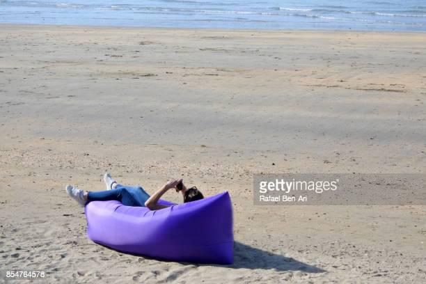 young woman lying on an air mattress on an empty beach - rafael ben ari bildbanksfoton och bilder