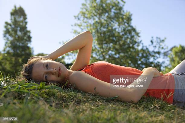 Young woman lying on back in grass, portrait