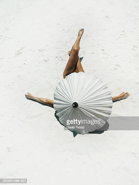 Young woman lying on back protected by parasol on beach, rear view