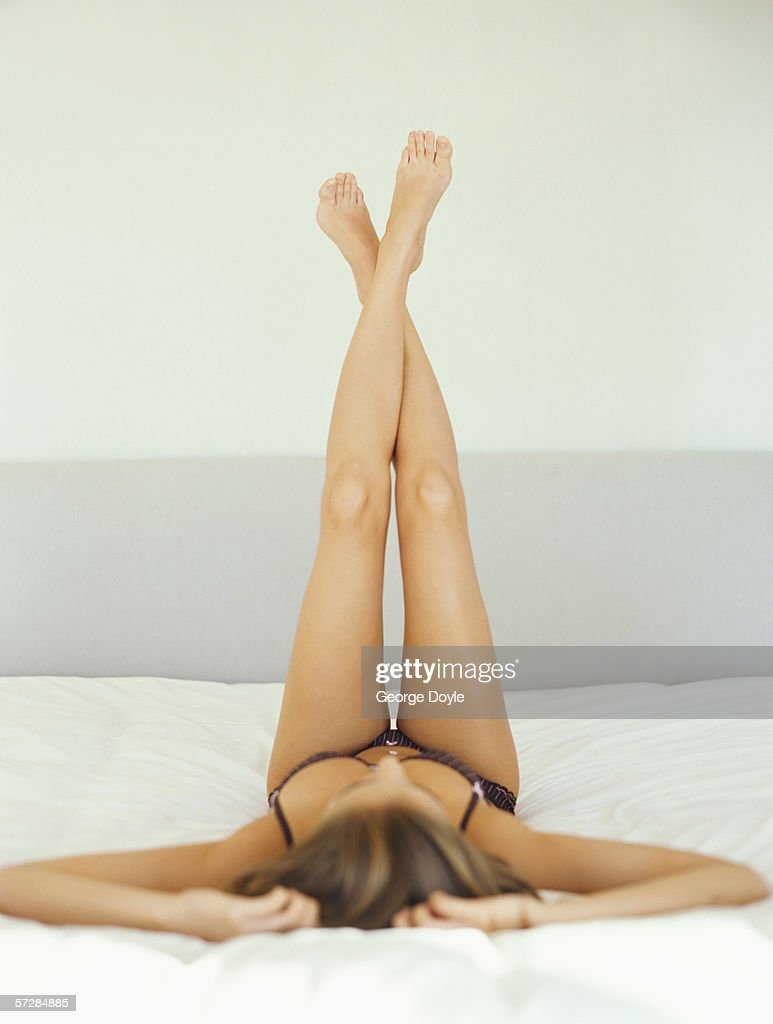 Young woman lying on back with  her legs crossed in the air : Stock Photo