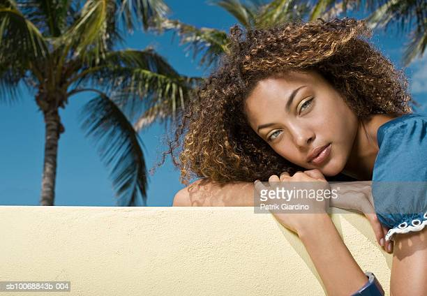Young woman lying on balcony, portrait, close-up