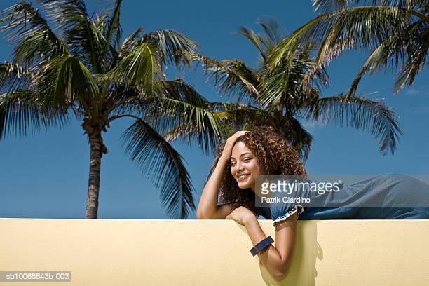 Young woman lying on balcony, smiling, close-up