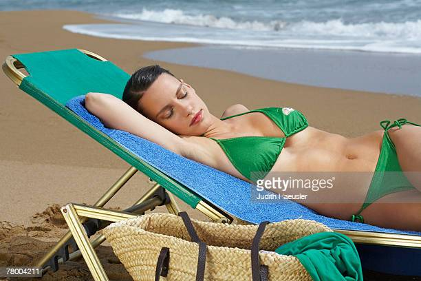 Young woman lying on beach chair with eyes closed.