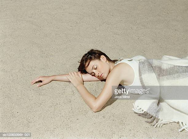 young woman lying on beach, eyes closed, elevated view - china foto e immagini stock