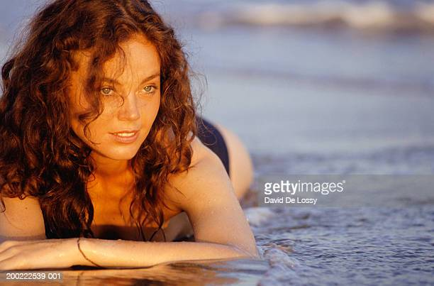 Young woman lying on beach in shallow water