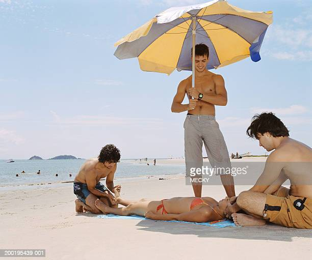 Young woman lying on beach, pampered by three young men