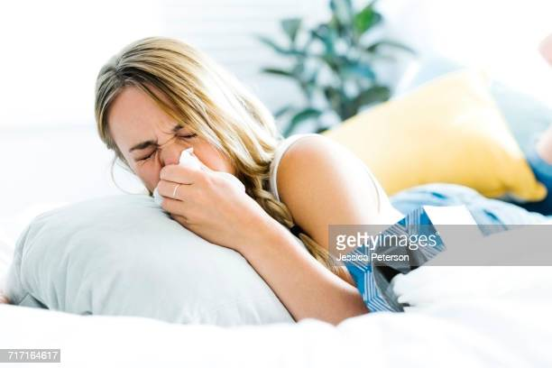 young woman lying on bed and blowing nose - cold and flu stock photos and pictures