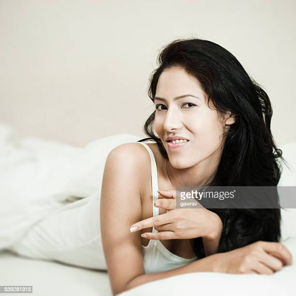 Young woman lying on bed and pointing two fingers.
