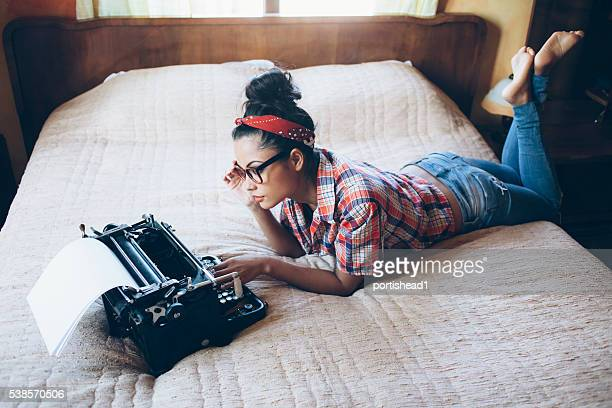 Young woman lying on bed and using typewriter