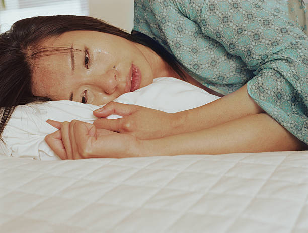 young woman lying on bed crying, close-up - asian woman crying on the bed stock pictures, royalty-free photos & images