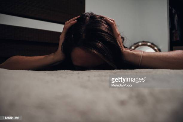 young woman lying on bed face down with ears covered - domestic violence stock pictures, royalty-free photos & images