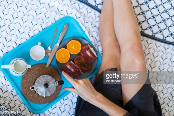Young woman lying on bed having breakfast, partial view