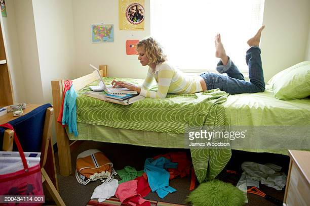young woman lying on bed in student dorm, using laptop computer - one young woman only stock pictures, royalty-free photos & images