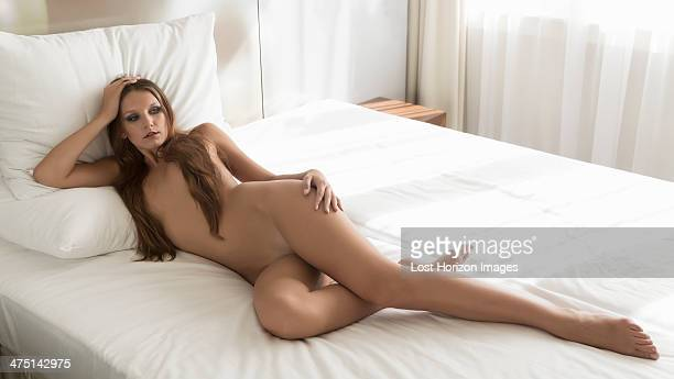 young woman lying on bed naked - desnudos femeninos fotografías e imágenes de stock