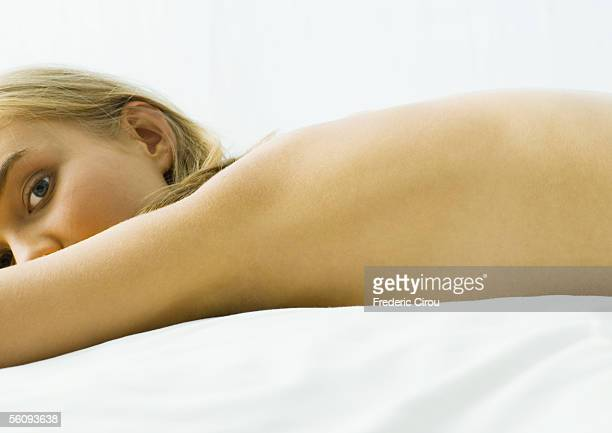 Young woman lying on bed nude