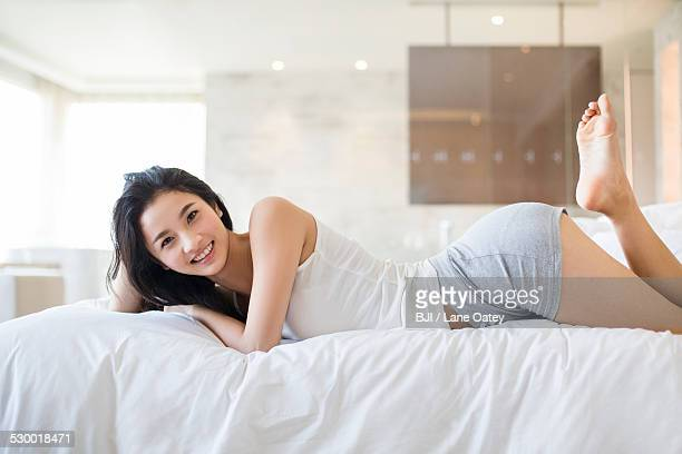 young woman lying on bed - 腹ばい ストックフォトと画像