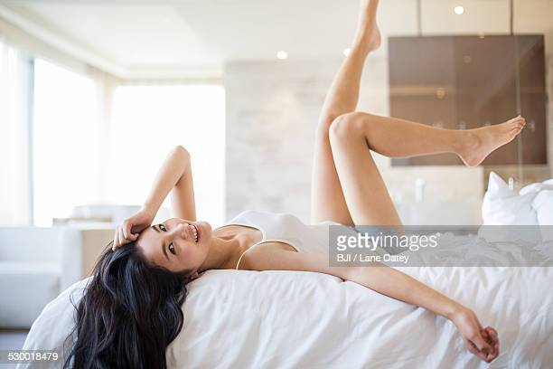 young woman lying on bed - beautiful asian legs stock photos and pictures