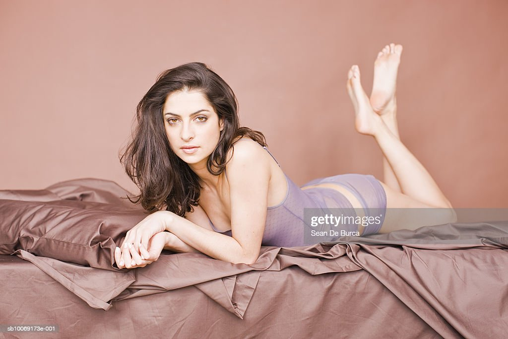 Young woman lying on bed, portrait : Stockfoto