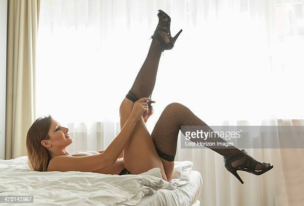 young woman lying on bed putting on fishnet stockings - höga klackar bildbanksfoton och bilder