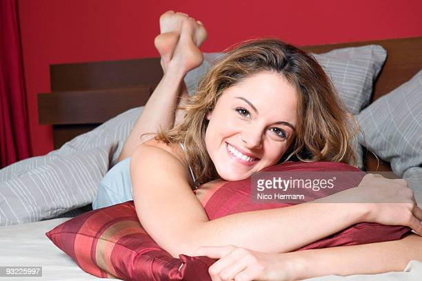 young woman lying on bed, smiling, portrait - woman lying on stomach with feet up stock photos and pictures