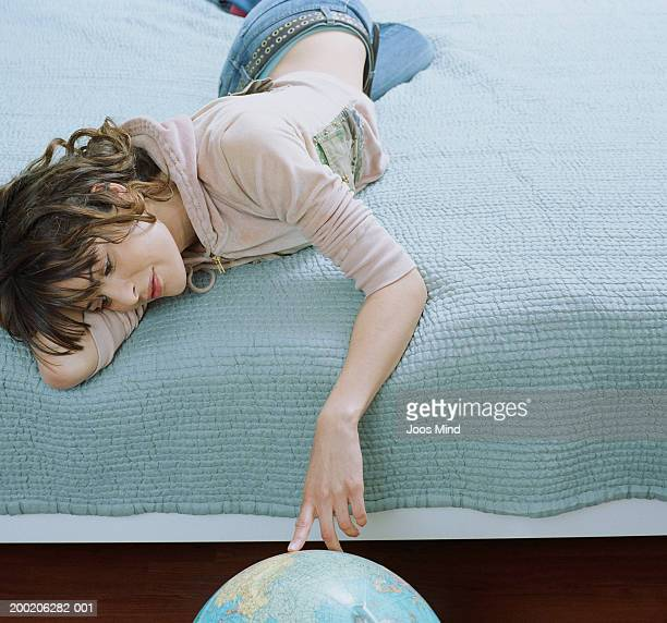 Young woman lying on bed, touching globe on floor