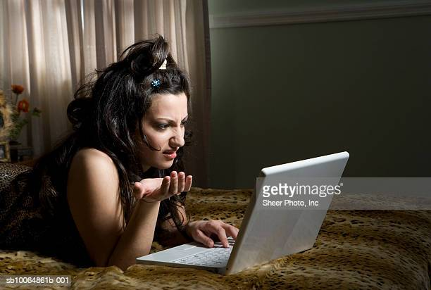 young woman lying on bed, using laptop and gesturing - leopard print stock pictures, royalty-free photos & images