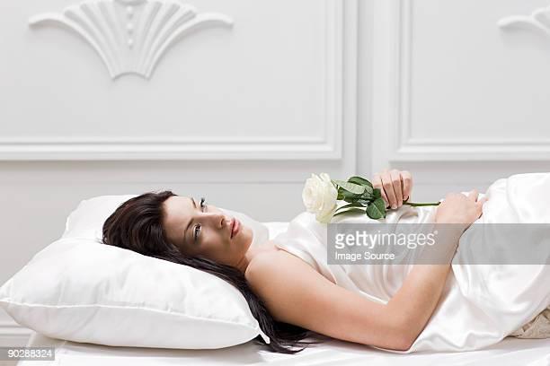 Junge Frau liegen im Bett mit rose